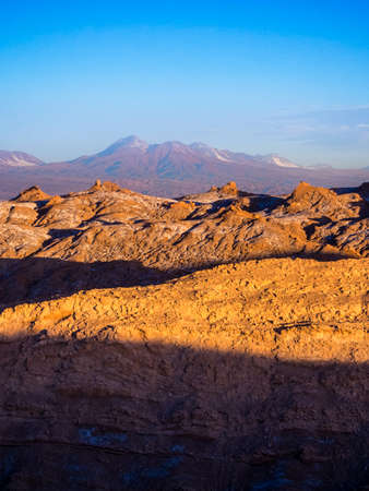 View of the Valley of the Moon in San Pedro de Atacama at sunset. In the background the volcano Licancabur and the Juriques, Chile
