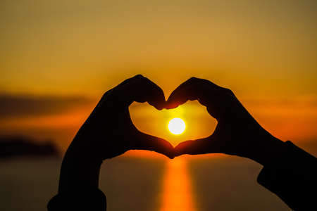 A heart made with hands with the sun inside it during sunset and sunrise, sunlight