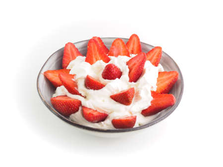 Strawberries with cream in a ceramic bowl with white background. Stock Photo