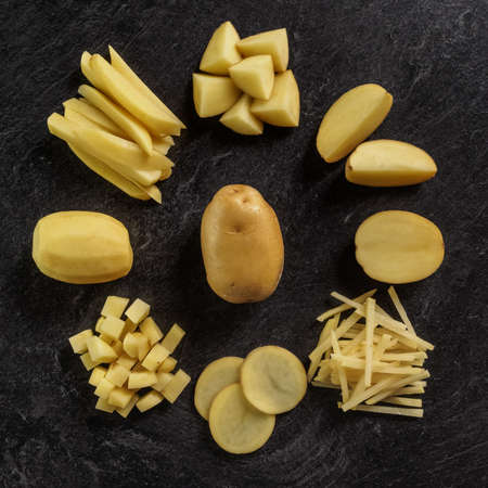 Different cuts of potatoes on a black textured background. Photo taken from above 写真素材