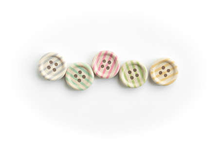 Wooden buttons with colorful stripes and colorful dots on a white background. Sewing 스톡 콘텐츠