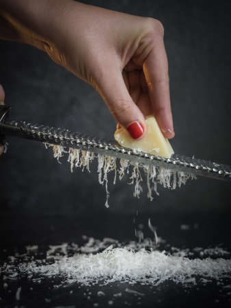 Hand of a woman grating parmesan cheese on a black background. Dark food. Italian cheese Parmigiano Reggiano Stock fotó