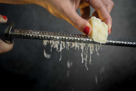 Hand of a woman grating parmesan cheese on a black background. Dark food. Italian cheese Parmigiano Reggiano Stock Photo