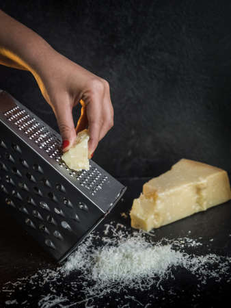 Hand of a woman grating parmesan cheese on a black background. Dark food. Italian cheese Parmigiano Reggiano Standard-Bild