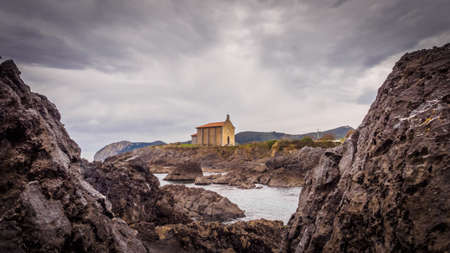 Small church of Santa Catalina on the coast of Mundaca village in Biscay during a cloudy day, Spain Stock Photo