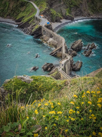 The coast from San Juan de Gaztelugatxe, Dragon-stone in Game of Thrones, bridge and stone stairs. Yellow flowers in spring and summer Stok Fotoğraf