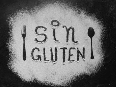 Gluten free flour with text gluten free in Spanish language with spoon and fork silhouette made with flour on dark texture background, up horizontal view