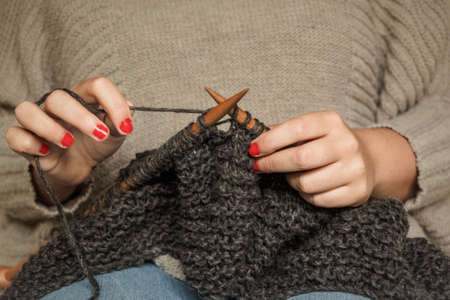 Girl with red nails knitting dark gray wool with wooden needles sitting in a chair, crafts with wool
