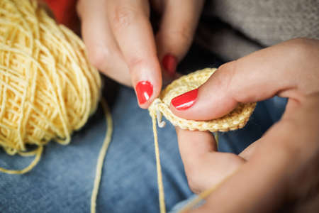 Girl doing crochet with yellow yarn and nails painted red, close up photography