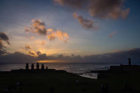 Silhouettes of Ahu Tahai moai in Hanga Roa, Easter Island in Chile during sunset