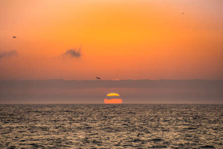 The sun hiding in the ocean with birds flying on the coast of Paracas in Peru. Фото со стока - 131992246