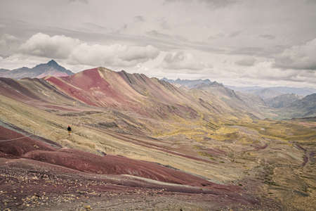 Rainbow mountain or Vinicunca in southern Peru. Lonely man doing trekking Фото со стока - 131992492