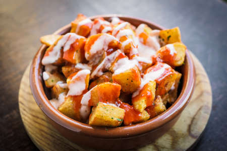 Spanish potatoes patatas bravas for tapas with tomato and spicy sauce on a bowl