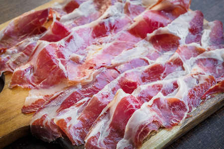 Iberico ham cut on a wooden board, spanish typical tapa