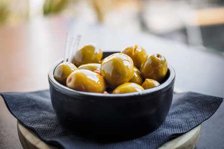 Green spicy olives spanish tapa on a black bowl Фото со стока - 131749913