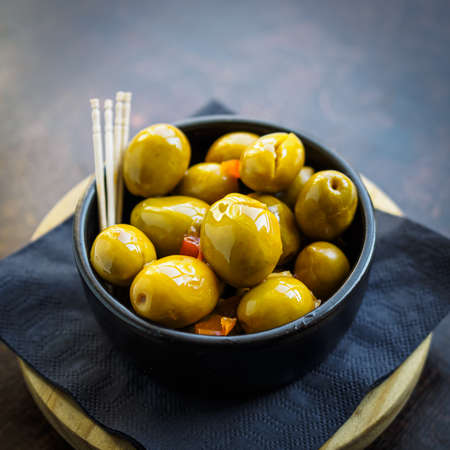 Green spicy olives spanish tapa on a black bowl Фото со стока