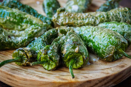 Fried Padron peppers tapa on a wooden board