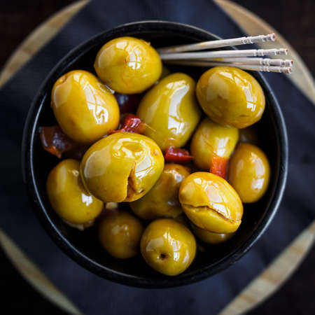 Green spicy olives spanish tapa on a black bowl Фото со стока - 131750178