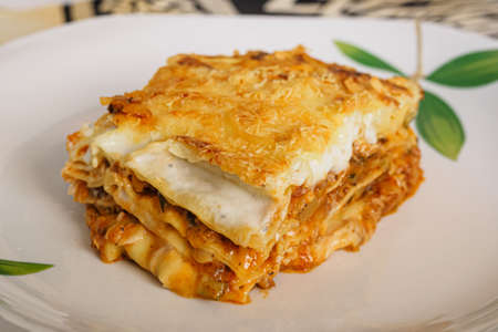 Portion of Italian lasagna stuffed with meat and vegetables, typical italian food