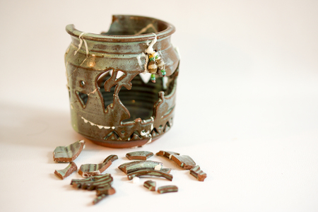 A broken decorative jar with pieces painstakingly glued together. Stock fotó