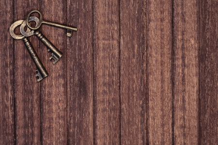 some old keys over a wooden background photo
