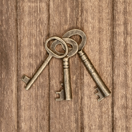 three old keys on a wooden background photo