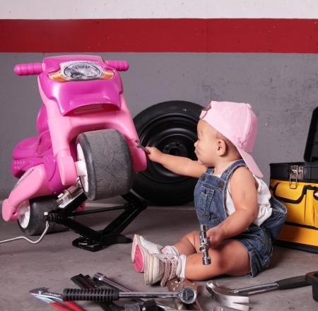 young beautiful baby working like mechanic photo