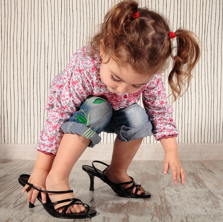 a little girl with mom shoes photo