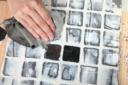 grout: worker applies grout at grey tiles