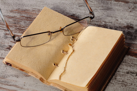 an old notepad and glasses on a wood table Stock Photo - 27302576