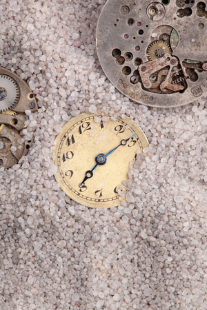 antique clocks buried in sand photo