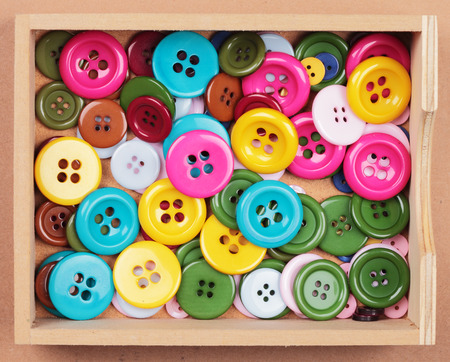 a collection with many buttons of different colors and sizes in a box photo
