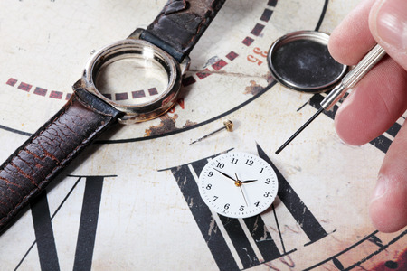 human repairing an old and broken clock photo