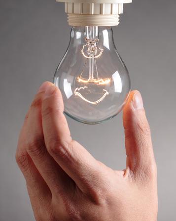 human hand changing a light bulb