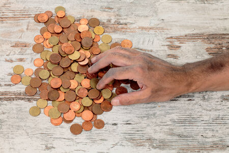 penury: a poor hands taking some coins Stock Photo