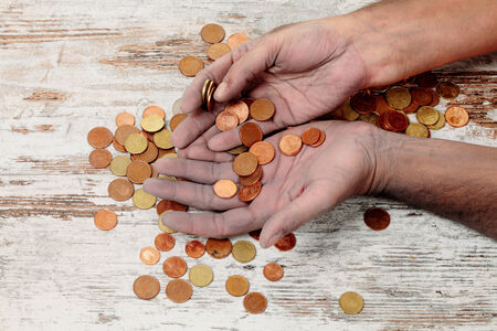 indigence: a poor hands taking some coins Stock Photo