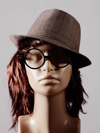 mannequin head with wig, hat and glasses photo