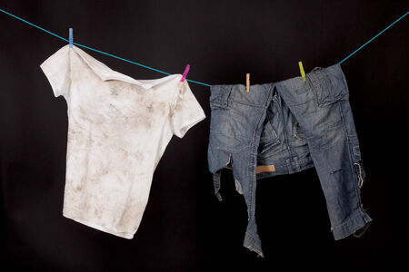 poorness: dirty shirt and trousers hanging to dry on a black background