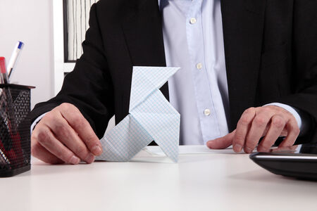 worker wasting time with origami photo