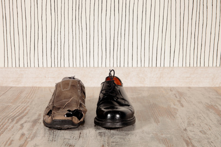broken foot: concept of rich and poor in a shoes
