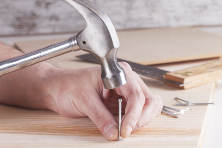 hammer head: detail of worker with a nail and a hammer