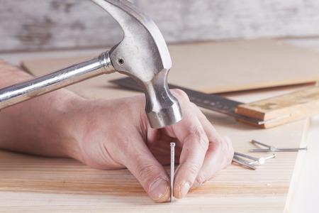 martillo: detalle de trabajador con un clavo y un martillo