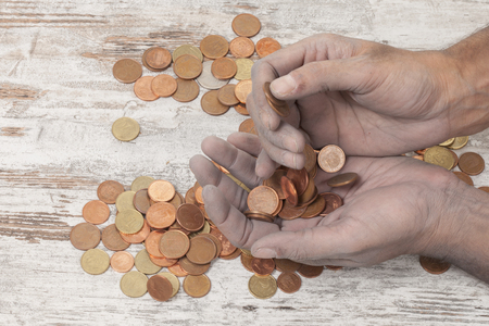 poor: a poor hands taking some coins Stock Photo