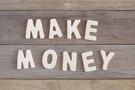 make over: The words make money over a wooden surface Stock Photo