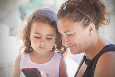 families together: Mother and daughter looking at her phone Stock Photo