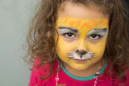 4 jaar oud meisje met het gezicht geschilderd als een tijger