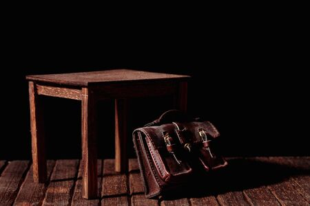 study table: a vintage bag under an old and wooden table Stock Photo