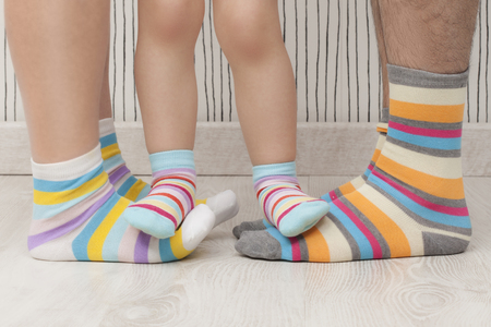 Mother, father and child wearing similar striped socks. Unrecognizable