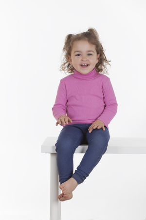 little girl sitting: Portrait of cute little girl sitting on bench and smiling. Studio shot. Isolated