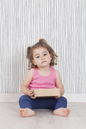 bare feet girl: Portrait of cute little girl sitting on floor and holding wooden box, closely looking at camera. Studio shot. Stock Photo